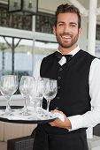 Handsome waiter holding tray of wineglasses in the patio of restaurant