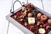 Candles on vintage tray with coffee grains and spices, bumps on color wooden background