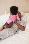 pic of babygro  - Father and baby girl lying on bed together at home in the bedroom - JPG