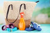 Summer wicker bag with accessories on nature background