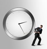 Businessman moving towards the clock