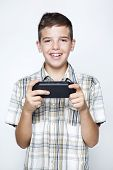A teen boy playing video games in a portable game console against gray background
