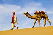 Indigenous Indian man walking through the desert with his camel.