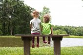 Sisters sitting on a bench at a pond