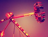 image of carnival ride  - a fair ride shot with a long exposure at nigh toned with a grungy retro vintage instagram filter  - JPG