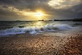 Splashing Sea Wave On Gravel Beach Against Sun Set Sky And Commercial Ship Port