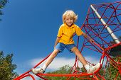 stock photo of legs apart  - Smiling boy stands on red rope with legs apart and holds rope with one arm - JPG