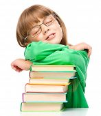 Cute little girl is sleeping on her books, isolated over white