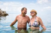 Senior couple enjoying the retirement on a seacost, having a swim in the sea, laughing togther, stay