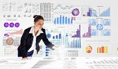 image of stock market data  - Young businesswoman analyzing data information of market - JPG