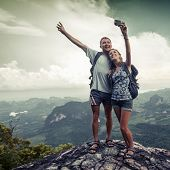Couple of hikers taking photo of themselves on top of the mountain with green valley on the backgrou