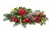Christmas decoration with red bauble, holly, ivy, mistletoe, fir and cedar leaf sprigs with snow cov