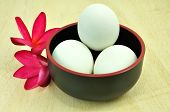 stock photo of duck egg blue  - eggs in black cup on wood background - JPG