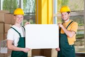 Warehouse Workers Holding A Blank White Board