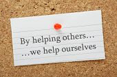 stock photo of helping others  - The phrase By helping others we help ourselves typed on a piece of lined paper pinned to a cork notice board - JPG