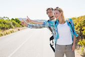 Attractive couple standing on the road hitch hiking on a sunny day
