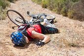 Injured cyclist lying on ground after a crash on a sunny day