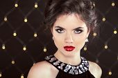 Stare. Elegant Brunette Woman Lady With Makeup And Hairstyle. Fashion Girl Model Over Lights Backgro