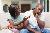 Unhappy couple having an argument on the couch at home in the living room