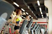 Lovely girl posing on treadmill in gym