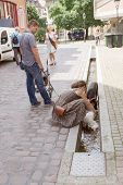 FREIBURG IM BREISGAU, GERMANY - AUGUST 6, 2014: Old town street in Freiburg, a city in the south-western part of Germany in the Baden-Wurttemberg state. Woman washes a child in the street channel
