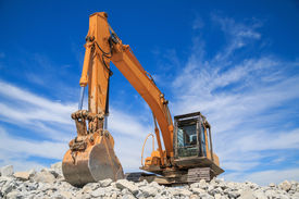 stock photo of power-shovel  - Yellow excavator at construction site against blue sky - JPG