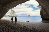 Couple taking pictures at scenic Cathedral Cove New Zealand