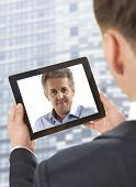 Cropped image of businessman attending video conference with colleague on digital tablet