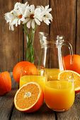 Glass of orange juice with slices and flowers on rustic wooden background