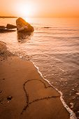 Waves Washing A Heart Drawn On The Beach Sand Away