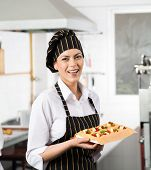 Happy female chef holding tray with stuffed ravioli pasta sheet in commercial kitchen