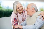 Smiling senior couple looking at each other while using laptop at nursing home