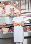 Portrait of male and female butchers at display counter in butchery