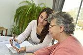 Home helper taking care of elderly woman's paperwork