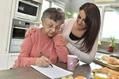 Elderly woman doing crossword while homecare helps at home