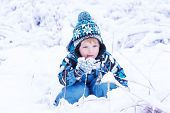 Little Toddler Boy Having Fun With Snow Outdoors On Beautiful Winter Day. Funny Playing With Snow An