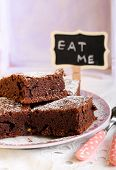 stock photo of eat me  - dusted with icing sugar on plate and a sign saying Eat Me - JPG