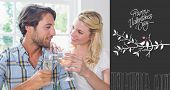 Cute smiling couple enjoying white wine together against cute valentines message