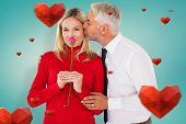 Handsome man giving his wife a kiss on cheek against blue vignette background