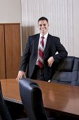 Happy Mid-adult Hispanic Businessman In Boardroom