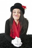 An otherwise  pretty teen girl curls her lips for a kiss.  Her face is adorned with rhinestones and sparkly red hearts. She  wears a black top hat, red scarf and white gloves.  On a white background.