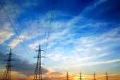 stock photo of power transmission lines  - Pylons and power lines at sunset with vibrant skyclouds and sun - JPG