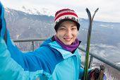 Female skier taking selfie.