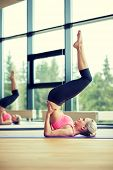 fitness, sport, training and people concept - woman doing shoulderstand on mat in gym