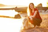 Young woman with shih-tzu dog sitting on lake shore. Red sunset light.