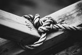 Rope with node on wooden beam. Black and white film style colors.