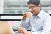 Asian Indian businessman using laptop computer while drinking a cup hot milk tea.