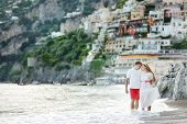 Smiling Happy Young Couple Walking On Positano Beach