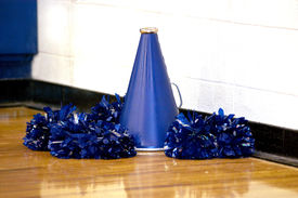 image of pom poms  - Cheerleading megaphone and pompoms sit on the wooden gymn floor  - JPG