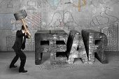 stock photo of overcoming obstacles  - Businessman holding sledgehammer hitting 3d fear mottled concrete word with business doodles wall background overcoming fear concept - JPG